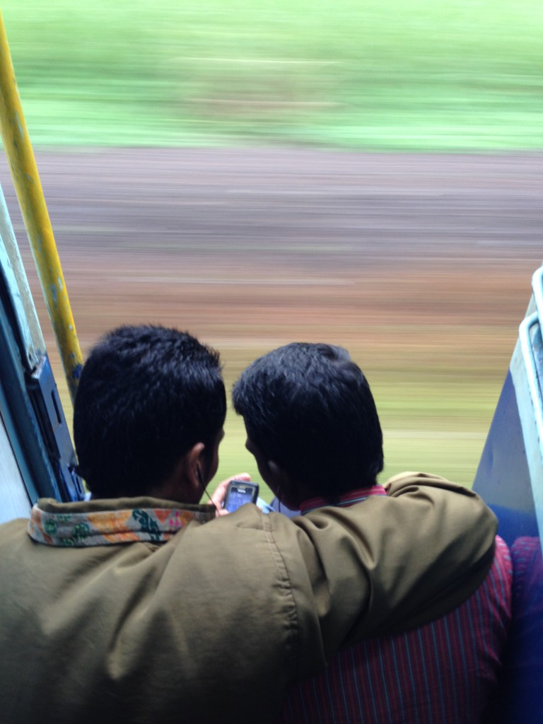 Two guys sharing headphones watching a bollywood clip